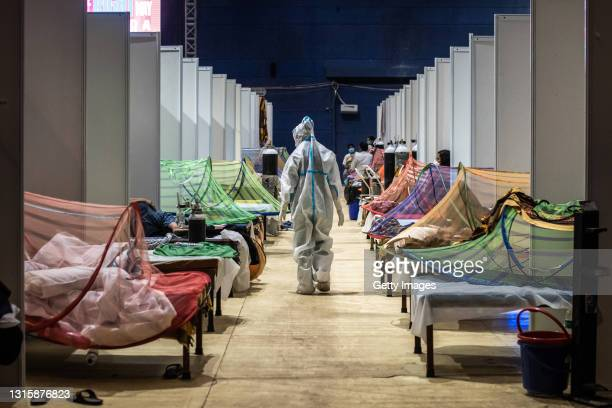 Medical worker in PPE observes patients who have been infected by Covid-19 inside a makeshift covid care facility in a sports stadium at the...