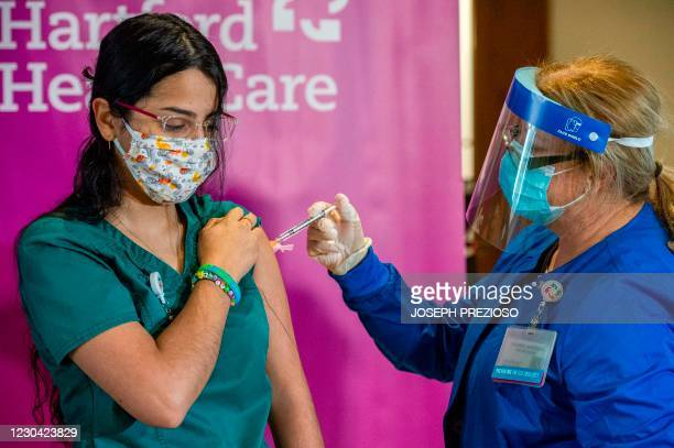 Medical worker Jasmine Ortiz is given the the second dose of the Pfizer/BioNTech vaccine twenty-one days after receiving the first shot from RN...