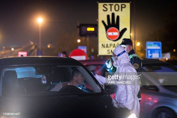 A medical worker measures body temperatures of motorists passing the SlovenianItalian border crossing near Nova Gorica on March 11 after Slovenia's...