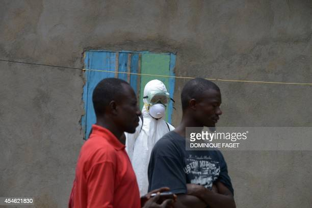 A medical worker member of the Liberian Red Cross wears a protective suit while watching local residents in Banjor some 30 kilometers from the...