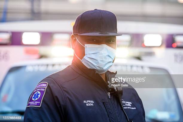 A medical worker poses for a portrait outside NYU Langone Health hospital as people applaud to show their gratitude to medical staff and essential...