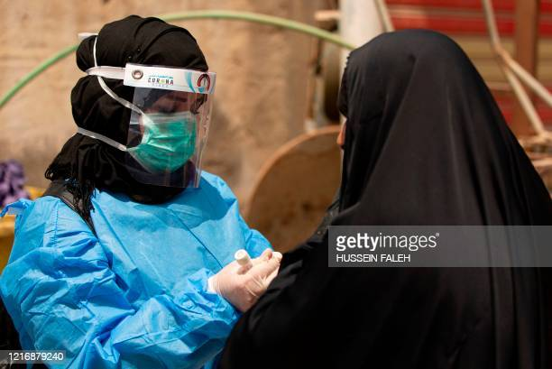 Medical worker prepares to take a swab from a woman being tested for COVID-19 coronavirus disease, in the 5-Miles district of Iraq's southern Basra...