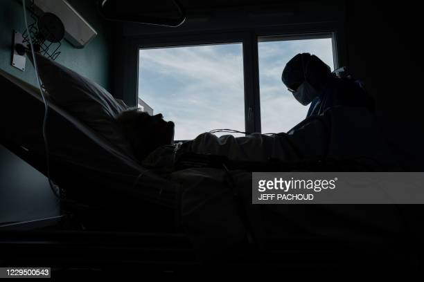 """Medical worker provides care to a patient infected with Covid-19 disease caused by the novel coronavirus in the Covid-19 unit of the """"Hopital Prive..."""