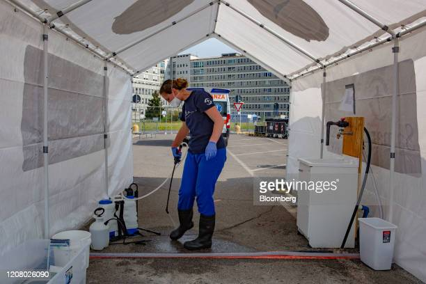 A medical worker sanitizes her boots at field hospital to be run by nongovernmental organisation Samaritan's Purse outside of Cremona hospital in...