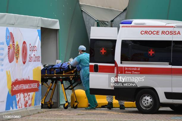 A medical worker stretches a patient from an Italian Red Cross ambulance into an intensive care unit set up in a sports center outside the San...