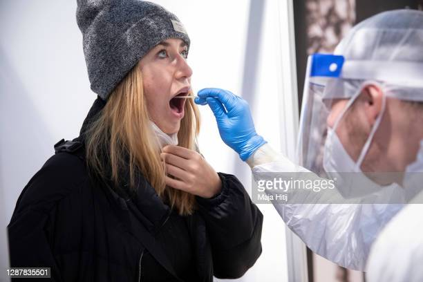 Medical worker takes a Covid-19 throat swab sample from a passenger at a testing station for Covid-19 at Berlin-Brandenburg Airport during the second...