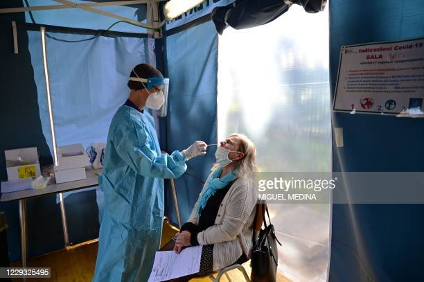A medical worker takes a nasal swab from a woman swab at a drivethrough Covid19 screening area in the triage of the San Carlo hospital in Milan on...