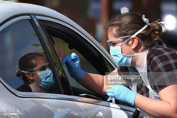 A medical worker takes a swab at a drivein COVID19 testing centre at Chessington World of Adventures Resort theme park on April 24 2020 in...
