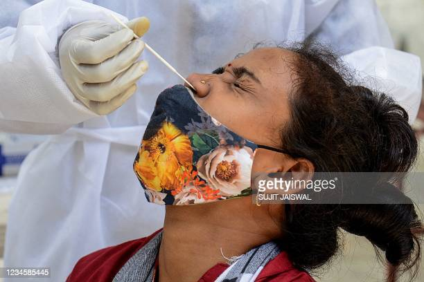 Medical worker takes a swab sample from a woman during a Covid-19 coronavirus screening in Mumbai on August 9, 2021.