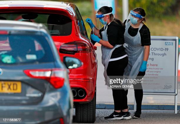Medical worker takes a swab to test for the novel coronavirus COVID-19 from a visitor to a drive-in testing facility at the Chessington World of...