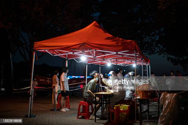 Medical worker takes samples during a mass Covid-19 test in a residential block on August 6, 2021 in Wuhan, Hubei Province, China. Local media has...