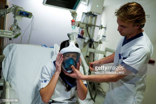 Medical worker tests a Decathlon snorkeling mask upgraded with 3D-printed respiratory valves fittings on March 27, 2020 at the Erasme Hospital in...