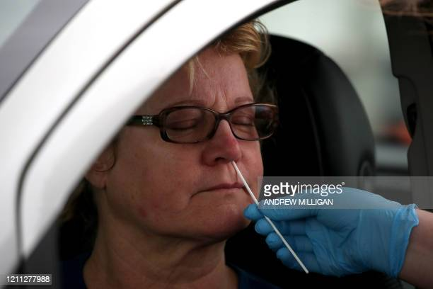 Medical worker tests a key worker for the novel coronavirus Covid-19 at a drive-in testing centre at Glasgow Airport on April 29 as the UK continues...