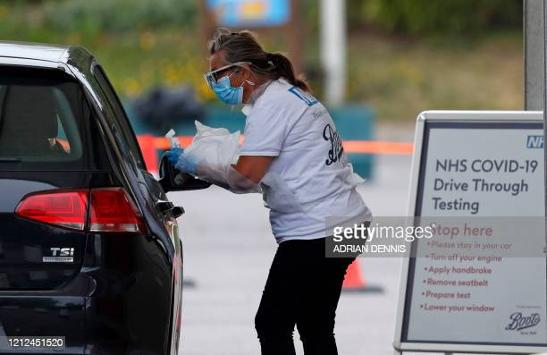 Medical worker tests a key worker for the novel coronavirus Covid-19 at a drive-in testing centre set up in the car park of Chessington World of...