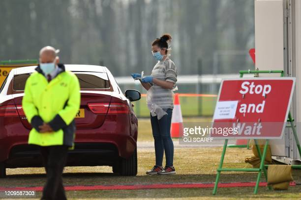 A medical worker tests a NHS worker at a drivein testing station for the novel oronavirus COVID19 at Haydock Park Racecourse in Merseyside North West...