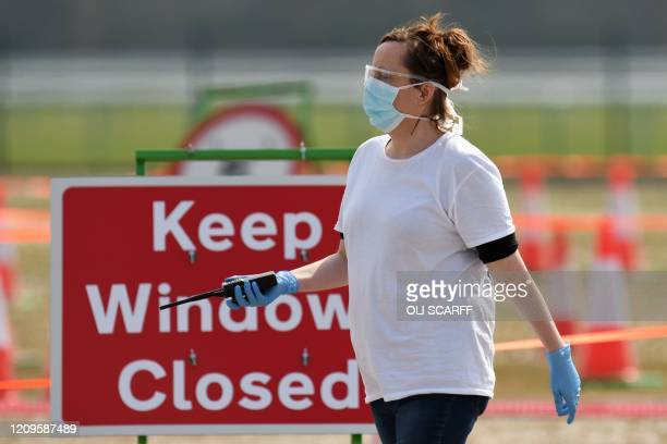 A medical worker walks at a drivein testing station for the novel oronavirus COVID19 at Haydock Park Racecourse in Merseyside North West England on...
