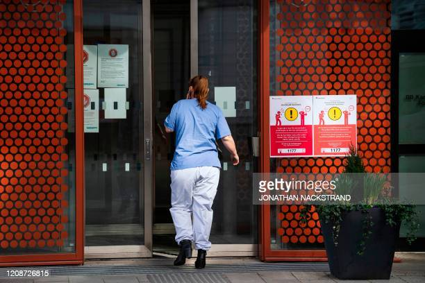 A medical worker walks in the entrance with an information sign to help minimising the spread of the novel coronavirus COVID19 hung up at Karolinska...