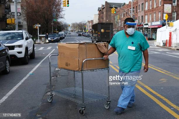 A medical worker walks outside of a special coronavirus intake area at Maimonides Medical Center on April 07 2020 in the Borough Park neighborhood of...