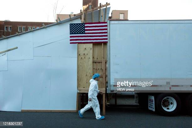 Medical worker walks past a refrigerated truck next to Wyckoff Heights Medical Center on April 11, 2020. In New York City. The global number of...