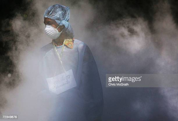 Medical worker walks through dry ice vapour at a makeshift morgue inside a Buddhist temple on January 2 2005 in Takuapa Thailand The bloated and...
