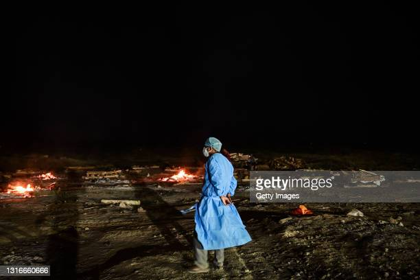 Medical worker watches cremations of the bodies of Covid-19 victims on the banks of the Ganges river May 06, 2021 in Allahabad, Uttar Pradesh, India....