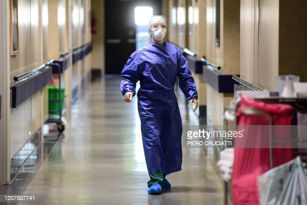 A medical worker wearing a face mask and gear walks across a unit of the Brescia Poliambulanza hospital Lombardy on March 17 2020