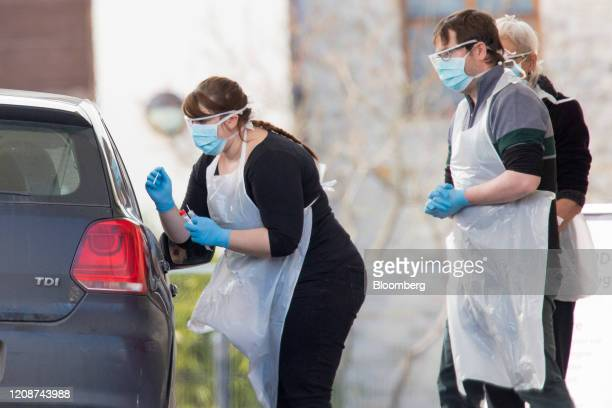 A medical worker wearing a protective face mask and screen disposable gloves and a plastic apron takes a swap at a coronavirus drivethrough testing...