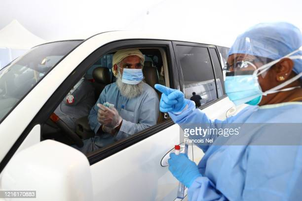 Medical worker, wearing a protective face mask and screen, disposable gloves and a plastic apron, takes a swap at a coronavirus drive-through...