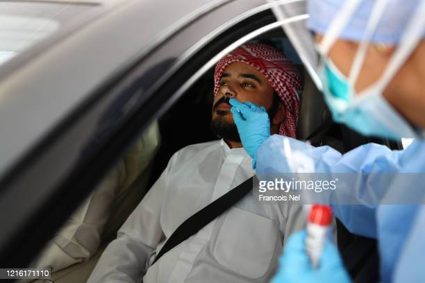 Medical worker, wearing a protective face mask and screen, disposable gloves and a plastic apron, takes a swab at a coronavirus drive-through...