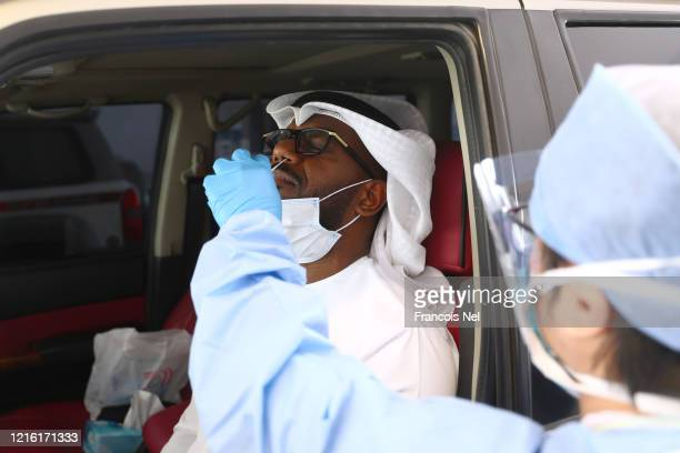 A medical worker wearing a protective face mask and screen disposable gloves and a plastic apron takes a swab at a coronavirus drivethrough screening...