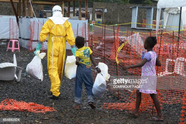 Medical worker wearing a protective suit carries bags followed by Ebola infected children in the high-risk area of the Elwa hospital runned by...