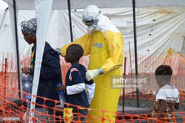 Medical worker wearing a protective suit leads a mother and her children inside the high-risk area of the Elwa hospital runned by Medecins Sans...
