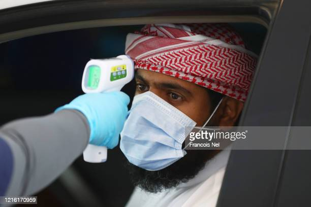 Medical worker, wearing disposable gloves , measures the temperature of a man at a coronavirus drive-through screening center on April 01, 2020 in...