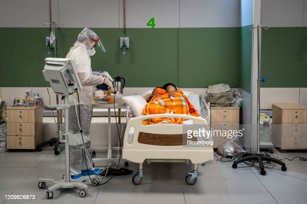 A medical worker wearing full personal protective equipment tends to a Covid19 patient beside a monitoring machine in a temporary coronavirus...