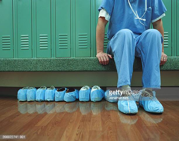 medical worker wearing overshoes in locker room, low section - protective workwear stock pictures, royalty-free photos & images