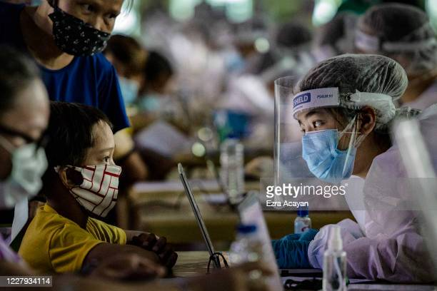 A medical worker wearing personal protective equipment interviews a child queueing for free COVID19 swab testing at a basketball court on August 6...
