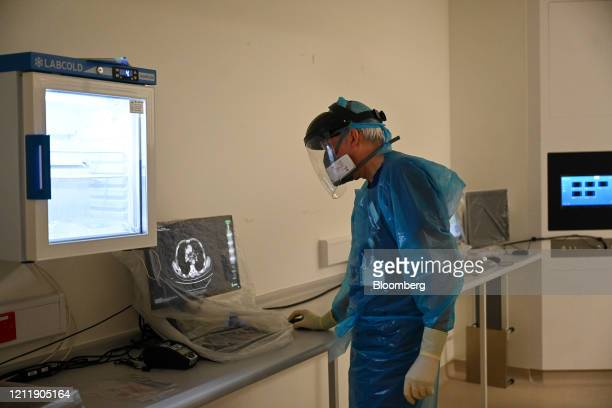 Medical worker wearing personal protective equipment looks at data on a monitor from a room in the Bronchoscopy unit at the Royal Papworth Hospital,...