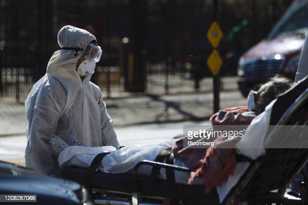 A medical worker wearing protective clothing pushes a stretcher outside the Elmhurst Hospital Center in the Queens borough of New York US on Thursday...