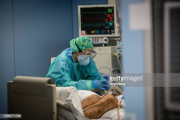 A medical worker wearing protective face mask goggles and scrubs tends to a patient on a ventilator diagnosed with Covid19 on the intensive care unit...