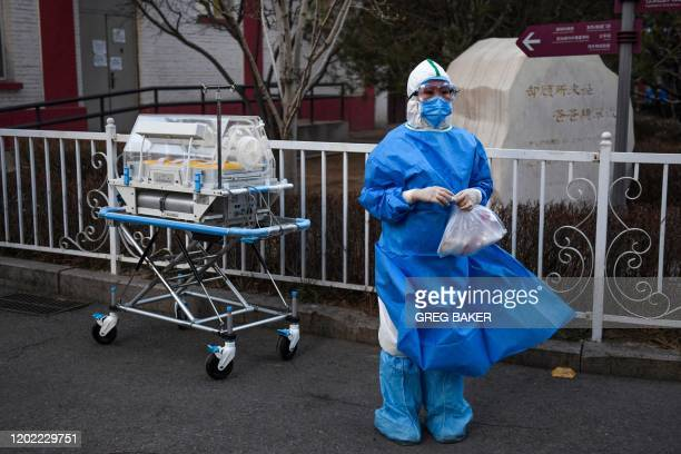 TOPSHOT A medical worker wears protective clothing as a preventive measure against the COVID19 coronavirus as she waits for a security guard to open...