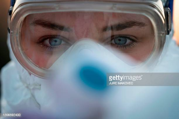 TOPSHOT A medical worker wears protective goggles as she prepares to measure motorists' body temperatures at the SlovenianItalian border crossing...