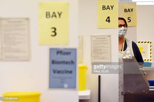 Medical worker works in a booth at a Covid-19 vaccination centre in Derby, central England on September 20, 2021. - Frontline health and social care...