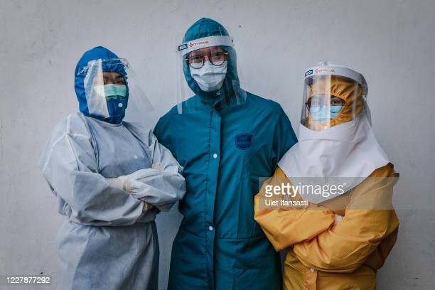 Medical workers, Agnesia, Yosua Herdyanto and Daisy pose for photograph during the virtual fashion show of personal protective equipment amid the...