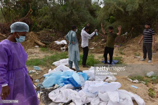 Medical workers and family members remove their PPE after the funeral ceremony of a person who died of COVID19 infection at Jadid Qabristan Ahle...