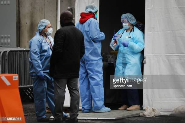 Medical workers and other officials gather outside of the Brooklyn Hospital Center where testing for the coronavirus has started on March 19 2020 in...