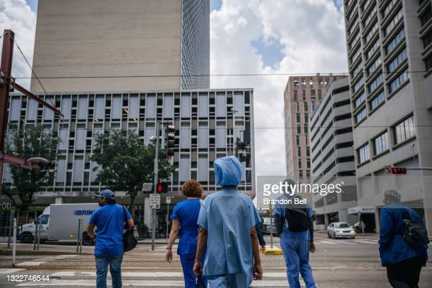 Medical workers and pedestrians cross an intersection outside of the Houston Methodist Hospital on June 09, 2021 in Houston, Texas. Houston Methodist...