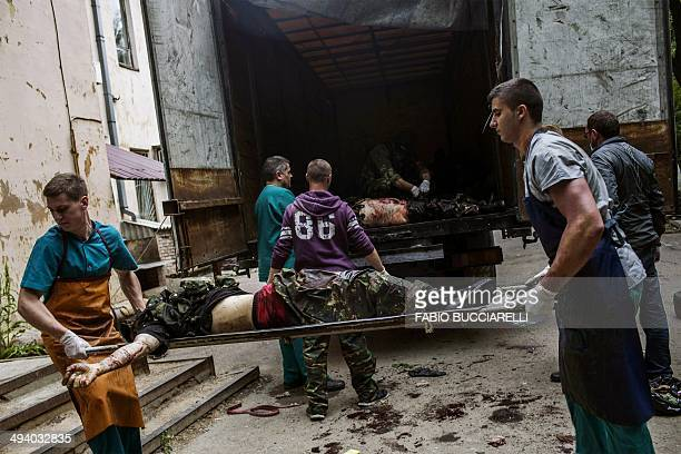 Medical workers and proRussian activists unload the bodies of killed proRussian fighters from a truck in the eastern Ukrainian city of Donetsk on May...