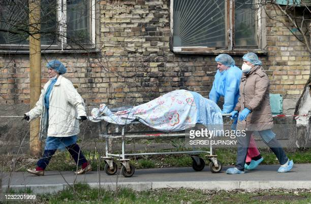 Medical workers carry a body on a stretcher from an hospital to the morgue in Kiev on April 9, 2021 as Ukraine registered this week a record number...