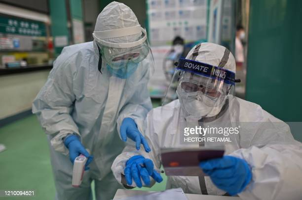 Medical workers check information as they take swab samples from people to be tested for the COVID-19 novel coronavirus in Wuhan, China's central...