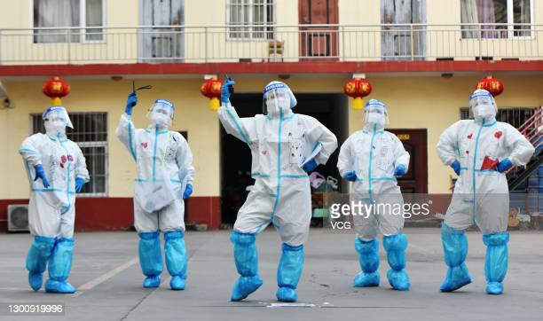 Medical workers cheer for residents who will conclude quarantine at a hotel and return home for Spring Festival holiday on February 7, 2021 in...